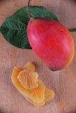 干芒果切片用在木背景的整个成熟果子 免版税库存图片