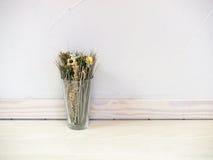 干花和草在玻璃花瓶对混凝土墙 库存照片