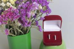 干花架花束在一块玻璃的白色表面上 附近有礼物的一个开放天鹅绒箱子 belove的耳环 库存照片