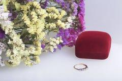 干花架花束在一块玻璃的白色表面上 附近有礼物的一个开放天鹅绒箱子 belove的耳环 免版税库存图片