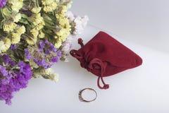 干花花束说谎白色表面上 其次与礼物的天鹅绒袋子 您心爱的圆环 库存照片