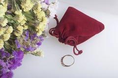 干花花束说谎白色表面上 其次与礼物的天鹅绒袋子 您心爱的圆环 免版税库存图片