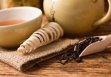 干茶在水壶和杯子附近生叶在黄麻布料 免版税图库摄影