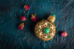 干茶玫瑰色芽和香水瓶 免版税库存照片