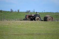 干草农夫打包的卷与古色古香的拖拉机的 库存图片