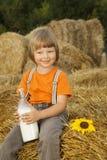 干草堆的孩子用面包和牛奶 免版税图库摄影