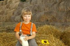 干草堆的孩子用面包和牛奶 库存图片