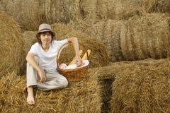 干草堆的少年用面包和牛奶 库存图片