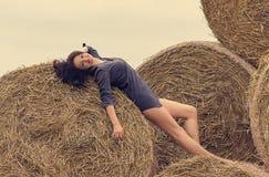干草堆背景的女孩  免版税库存照片