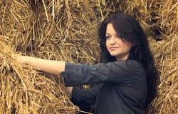 干草堆背景的年轻美丽的女孩  免版税库存照片