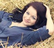 干草堆背景的年轻美丽的女孩  免版税库存图片