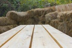 干草捆和木桌bacground 免版税图库摄影