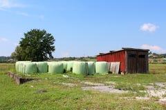 干草捆在塑料包裹了在木车库旁边围拢与未割减的草和大树与家庭房子在背景中 免版税图库摄影