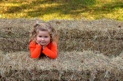 干草捆围拢的年轻微笑的女孩 库存图片