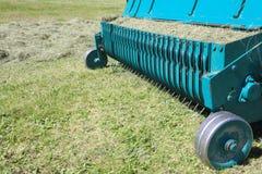 干草的农业设备割并且堆成行 免版税库存图片