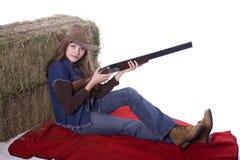 干草藏品猎枪坐的妇女 免版税库存图片