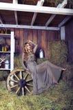 干草谷仓的美丽的白肤金发的时髦的女人 免版税库存照片