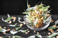 干菩提树花和叶子在一个透明玻璃碗在黑背景 背景弄脏了关心概念表面健康防护屏蔽的药片 免版税库存照片