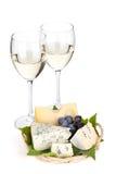 干酪、葡萄和二块白葡萄酒玻璃 库存照片
