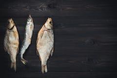 干鱼鲂和熔炼蜡烛鱼在黑暗的木桌上与拷贝空间 库存图片