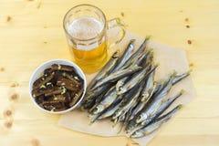 干鱼,大蒜油煎方型小面包片,一个玻璃杯子啤酒,顶视图 图库摄影