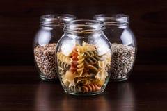 干麦子面团和五谷在一个瓶子的在黑暗的木背景特写镜头宏指令 免版税图库摄影