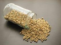 干黑眼豆或豆豇豆unguiculata或豇豆从棕色木表面上的一个玻璃瓶子倒 库存图片