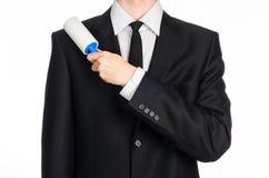 干洗和企业题材:拿着清洗的衣裳的一把蓝色稠粘的从尘土的一套黑衣服的一个人刷子和家具是 免版税库存图片