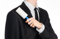 干洗和企业题材:拿着清洗的衣裳的一把蓝色稠粘的从尘土的一套黑衣服的一个人刷子和家具是 免版税图库摄影