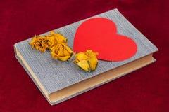 干黄色说谎在书的玫瑰和红色纸心脏 免版税库存照片