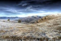 平原洒与在山的雪 免版税库存图片
