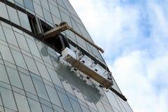 平台的窗口洗涤的工作者在摩天大楼的玻璃门面暂停了 库存图片