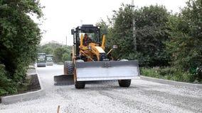 平地机挖掘机传播了在路的被击碎的石头