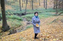 平均岁月的妇女反对一条小河的在秋天木头 免版税库存照片