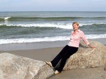 平均岁月的妇女坐冰砾 Balti的海岸 图库摄影