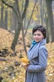 平均岁月的妇女的画象与黄色槭树的在手离开 免版税库存图片