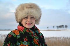 平均岁月的妇女的画象在一个毛皮盖帽和一件五颜六色的披肩的反对冬天湖 免版税库存照片