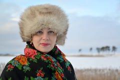 平均岁月的妇女的画象在一个毛皮盖帽和一件colorul披肩的反对冬天lakef 免版税库存图片