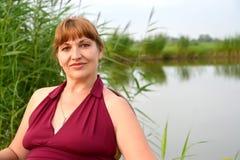 平均岁月的妇女的画象以湖为背景的 免版税库存图片