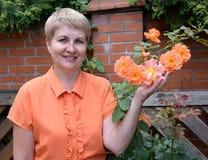平均岁月的快乐的妇女在一gardend显示一只玫瑰手在加尔德角 免版税图库摄影