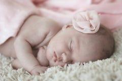平安地睡觉在一条桃红色毯子下的新出生的婴孩 图库摄影