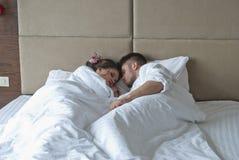 平安地睡觉在床上的年轻成人夫妇 免版税库存图片
