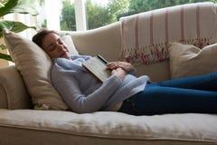 平安地睡觉在沙发的妇女 库存图片