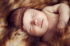 平安地睡觉在红色毛皮的新出生的婴孩 免版税库存图片