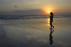 平安地走在日落的沙漠海滩的亚裔少妇在凝思和自由概念 免版税库存照片