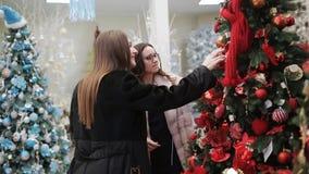 平安夜的两名妇女在一个购物中心选择圣诞节庆祝的圣诞装饰 股票录像