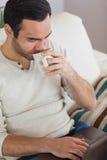 平安的可爱的人饮用的咖啡,当使用他的膝上型计算机时 免版税库存照片