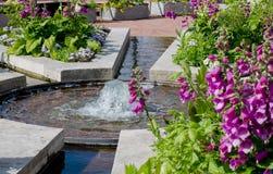 平安的喷泉在一个五颜六色的庭院里 免版税库存图片