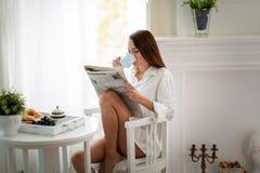 平安的少妇读书杂志在家 图库摄影