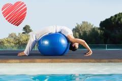平安的浅黑肤色的男人的综合图象眼镜蛇姿势的在锻炼球游泳池边 库存图片